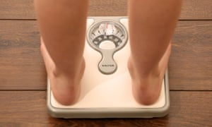 A person checks their weight on a set of bathroom scales