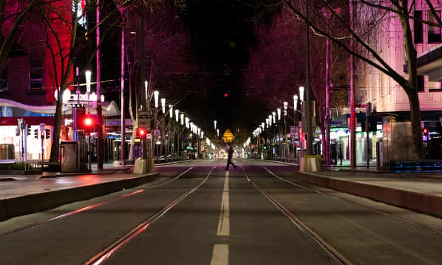 a man crosses an empty city street during Melbourne's nightly curfew