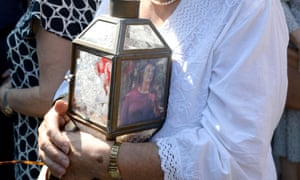 A woman holds a lantern with a picture of murdered journalist Daphne Caruana Galizia during a protest demanding justice.