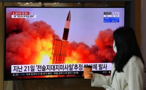 A woman walks past a screen showing file footage of a North Korean missile test