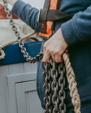 Crew member holding metal and rope cables aboard the Salford whelk boat.