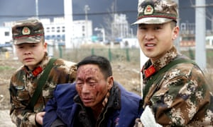 Police help an injured man after the explosion in Yancheng.