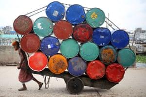Dhaka., Bangladesh  - A labourer transports used oil drums