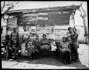The Elizalzabal and Silva families, who fish for a living, outside a family home on the shore of oil-contaminated Lake Maracaibo in Cabimas, Venezuela, 3 July