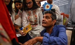 Mohammed Hanif gives autographs at an Islamabad literature festival in September 2019, after A Case of Exploding Mangoes was finally released in Urdu.