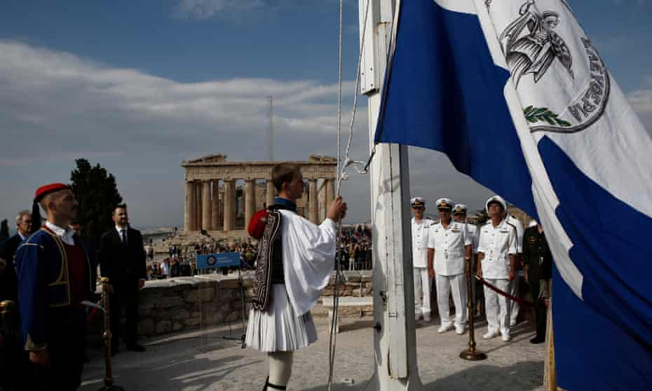 A presidential guard raises the historical Greek flag during a ceremony to mark the 74th anniversary of the liberation of Athens from Nazi occupation