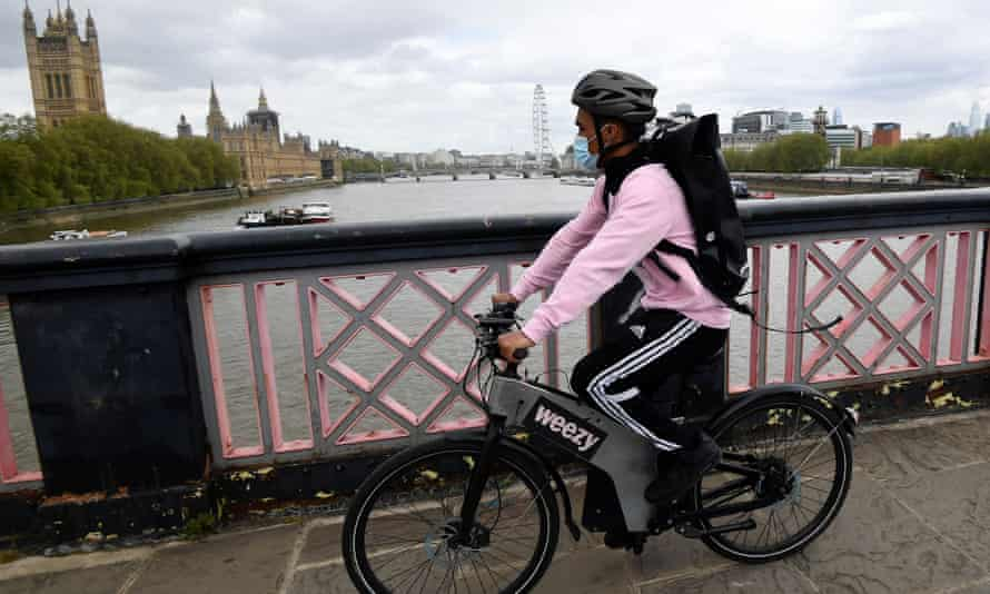A Weezy courier on a bicycle crosses the Thames in London.