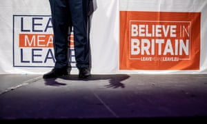 A man's legs in front of Leave Means Leave and Believe in Britain banners