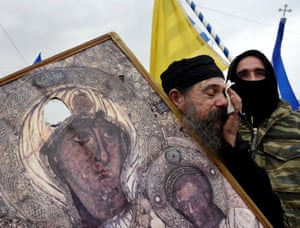 A priest holds a broken icon depicting the Virgin Mary holding the Christ child during the demonstration in Athens