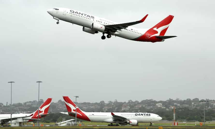 A qantas plane takes off above others parked on the tarmac