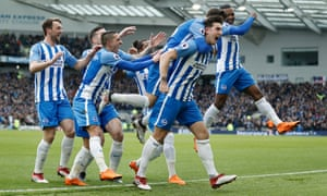 Brighton players swarm around Lewis Dunk after the defender opened the scoring against Arsenal.
