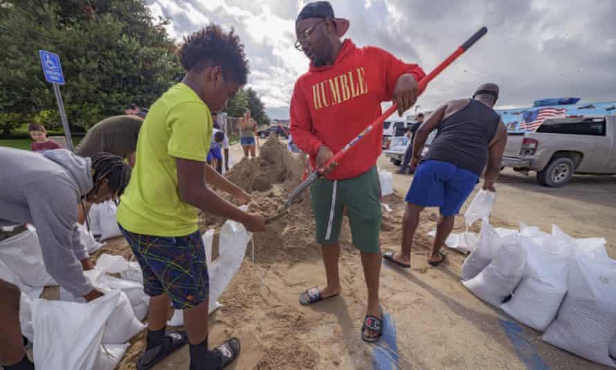 Jawan Williams shovels sand for a sandbag held by his son Jayden Williams, before landfall of Hurricane Ida in Chalmette, Louisiana, on Saturday.