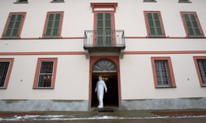 Doctor Luigi Cavanna stands at the entrance of a building as he waits for his assistant nurse Gabriele Cremona.
