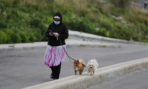 A domestic worker wearing a protective mask walks her employers' dogs before the nighttime curfew begins in Beirut, Lebanon.