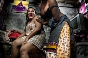 Hijras (Mumbai, India. 2017). Three Muslim transgender hijras in their room in a Bandra slum in Mumbai prepare for their evening and share jokes.