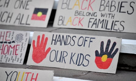 protest signs saying 'black babies belong with black families' and 'hands off our kids'