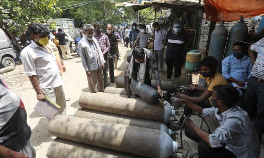 People queue to refill oxygen cylinders in New Delhi, India, 23 April.