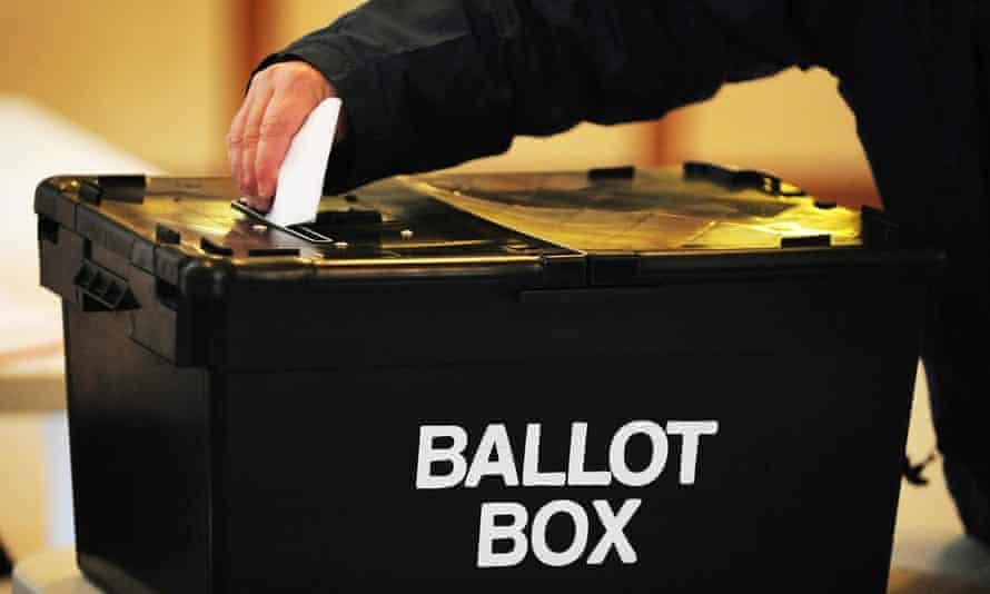 A voter placing a ballot paper in a ballot box.