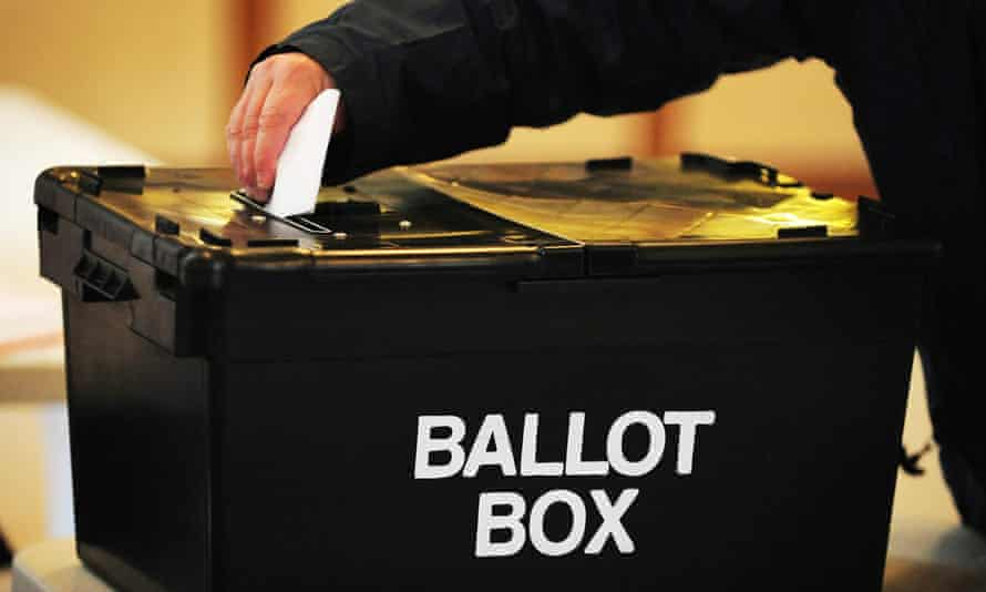 Hand putting a vote into a ballot box
