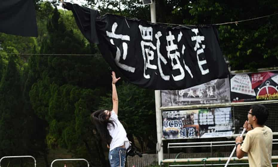 A woman tries to untangle a banner calling for independence, at the Chinese University of Hong Kong campus in Hong Kong. Universities have become the latest battleground over freedom.