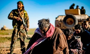 Suspected Isis fighters wait to be searched by the Syrian Democratic Forces