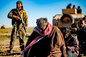 Men and boys suspected of being Islamic State (IS) group fighters wait to be searched by members of the Kurdish-led Syrian Democratic Forces (SDF) after leaving the IS last holdout of Baghouz