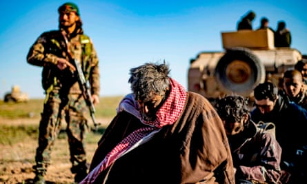Men and boys suspected of being Islamic State fighters wait to be searched by members of the Kurdish-led Syrian Democratic Forces.
