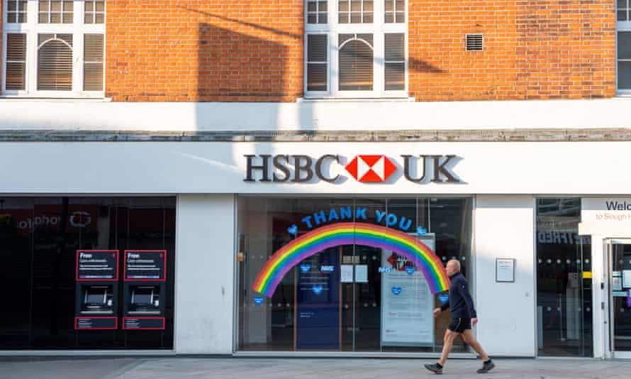A man walks past a Thank You rainbow in an HSBC bank window