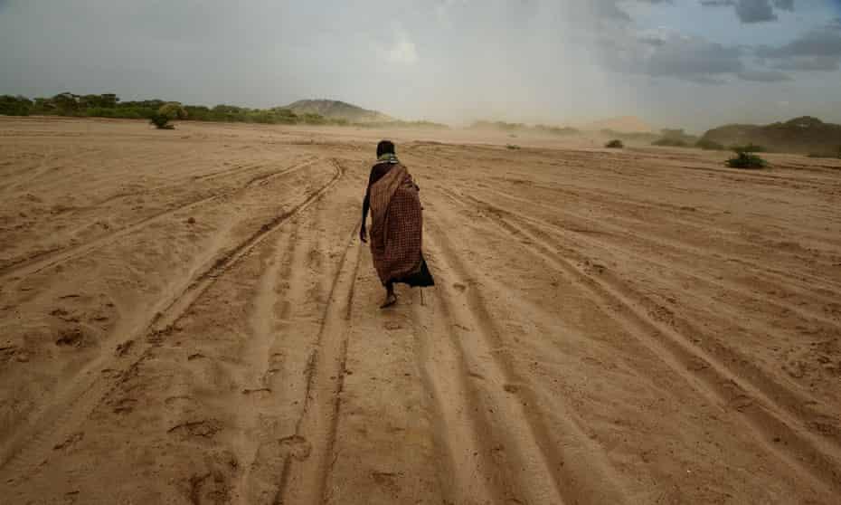 A woman walks across a dry riverbed in Turkana, Kenya.