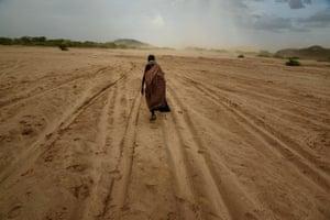 A woman walks across a dry riverbed in Turkana, Kenya on 18 October 2017