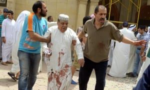 An injured man is helped after the mosque blast in Kuwait City