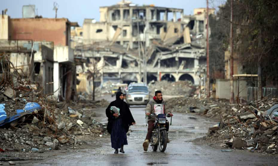 A Syrian woman walks next to a man riding a motorbike in Raqqa, the former de facto capital of the Islamic State (Isis) group, on 18 February.
