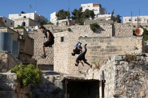Abdallah al-Natsheh, Usaid Abu Khalaf, and Hammam Abu Sneineh practise parkour in the West Bank city of Hebron.