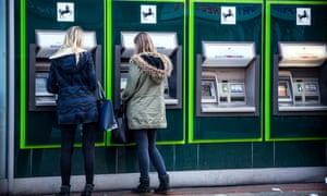 Two women at Lloyds bank cash machines