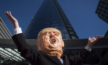 A protester outside the Trump International Hotel and Tower in Vancouver. Tens of thousands have signed a petition to have the Trump name removed from the building.