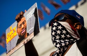A protestor in downtown Los Angeles holds up a picture of George Floyd