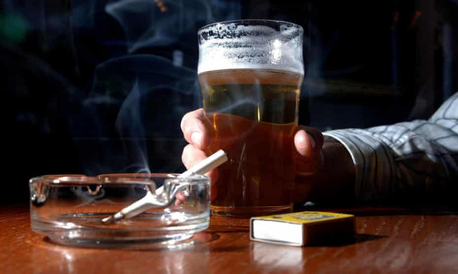 Cigarette in ashtray with pint glass
