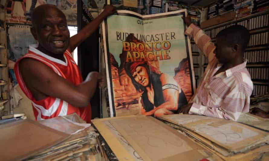 Employees in a Kinshasa video shop show their favourite film posters from Congo's golden age of cinema.