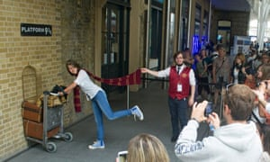 Tourists recreate Harry Potter at King's Cross station.