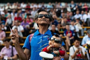 Hong Kong, China: a spectator holds a doll during the season opening horse race at the Sha Tin racecourse