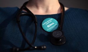 doctor wearing a badge next to her stethoscope in support of the junior doctor's contract