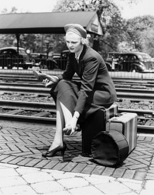 Woman at a train station changing shoes.