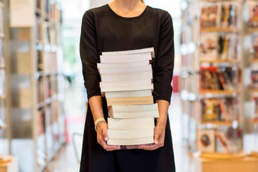 Woman holding stack of books