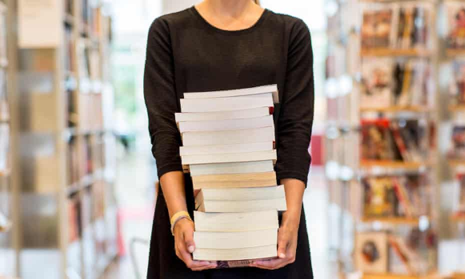 File photo of a young woman holding books in a library