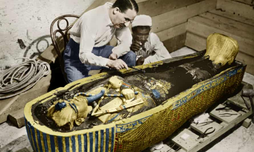 The British archeologist Howard Carter and an Egyptian assistant examine the sarcophagus containing the body of the pharaoh Tutankhamun in the Valley of the Kings, Egypt.