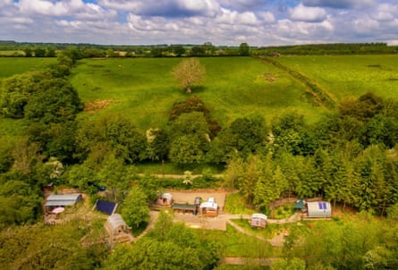 Daytime aerial view of Devon Dens cabins and the surrounding woodland.