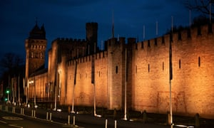 Wales flags fly at half mast at Cardiff Castle which has been illuminated in Wales.