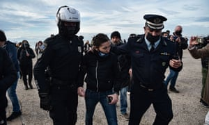 Police officers arrest a woman for trying to throw a cross into the sea in Thessaloniki, as Greek bishops' determination to keep churches open for today's Epiphany holiday in the face of a coronavirus lockdown have stepped up a confrontation with the government over health restrictions