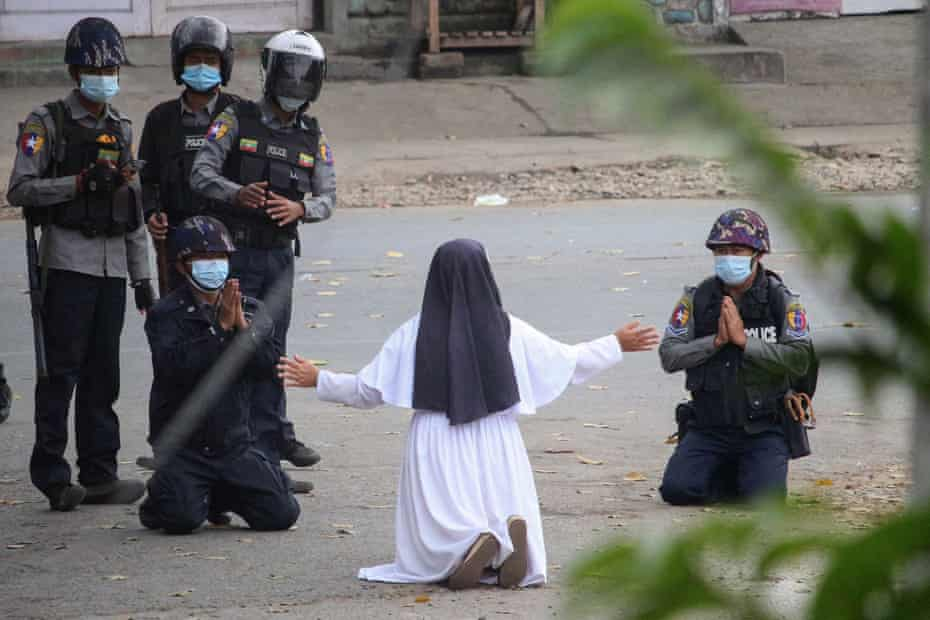 Sister Ann Rose Nu Tawng kneels in front of armed police