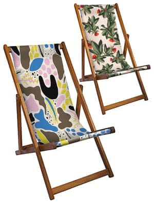 Two deckchairs, one with a multi-coloured swirly patterned seat, the other with a green leaves and red berries print